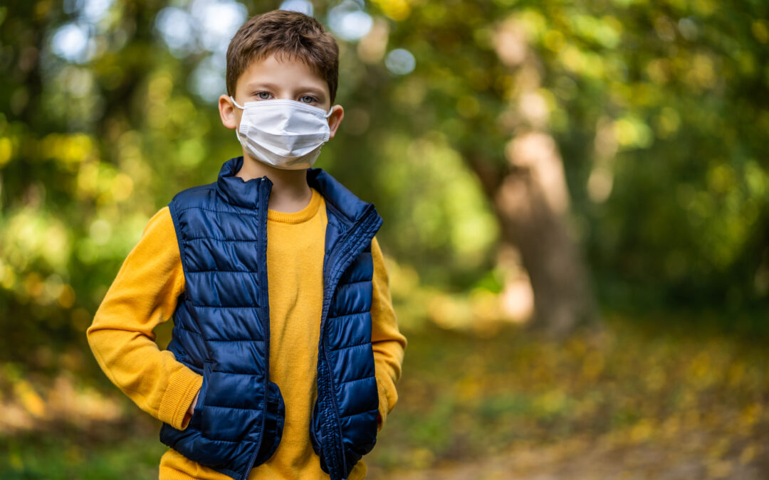Pictured is a young boy in a face mask. He is wearing a yellow shirt, blue puffer jacket and standing in the forest.